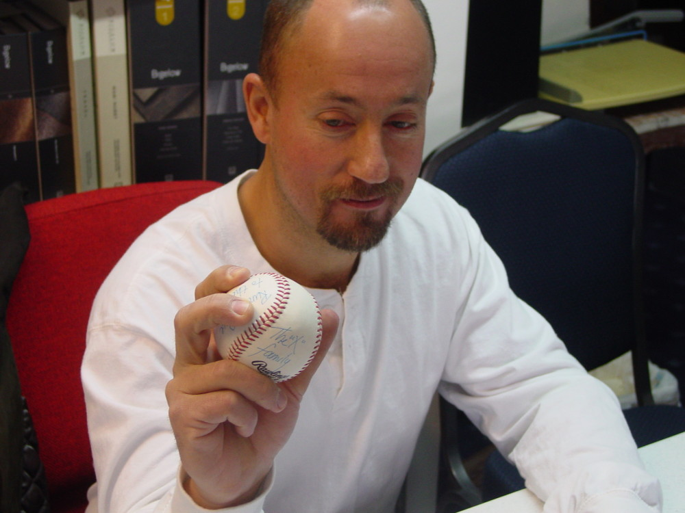 Man holding a baseball with prosthetic thumb